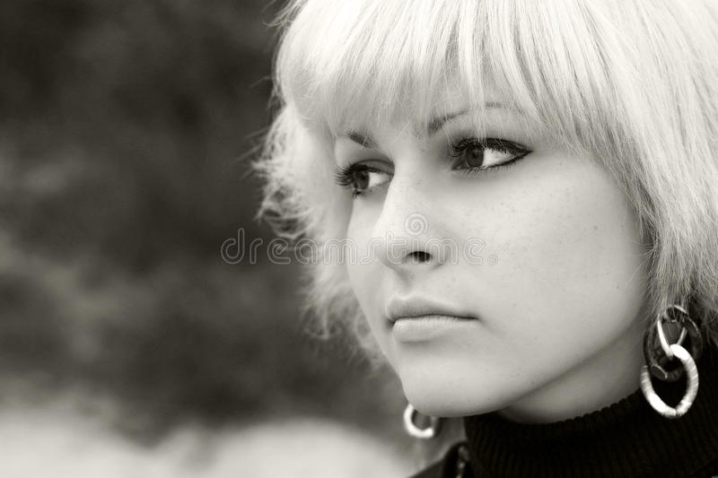 A blond girl looks in distance stock photo