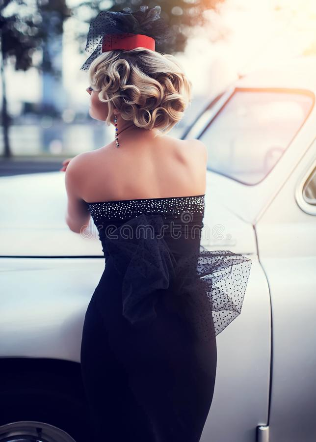 Blond girl model with bright makeup and curly hairstyle in retro style posing near old white car stock image