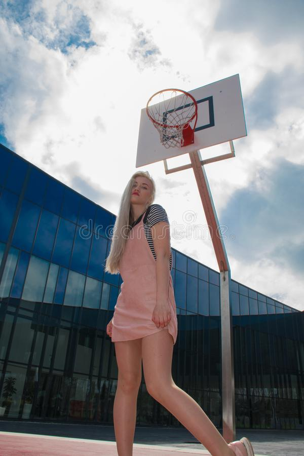 Blond girl near a mirror building stock photography