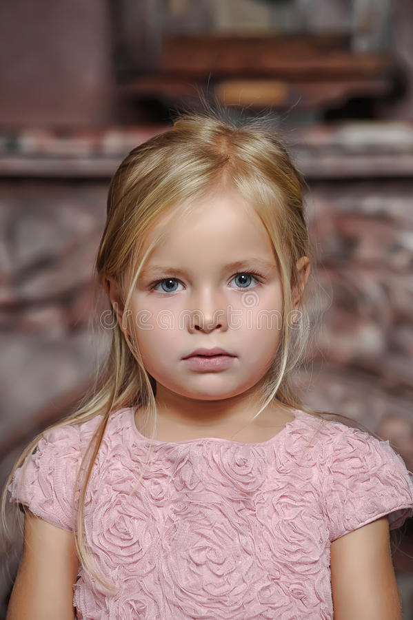 Blond girl in a pink dress royalty free stock images