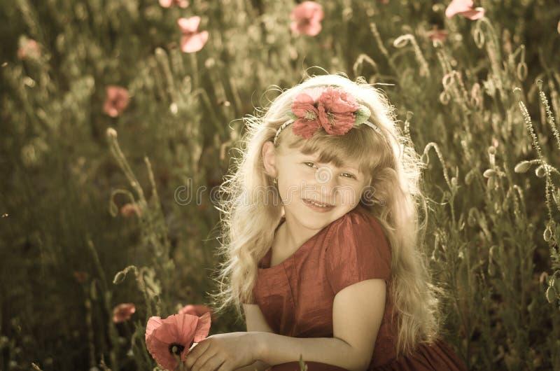 Blond girl in poppy field stock photo