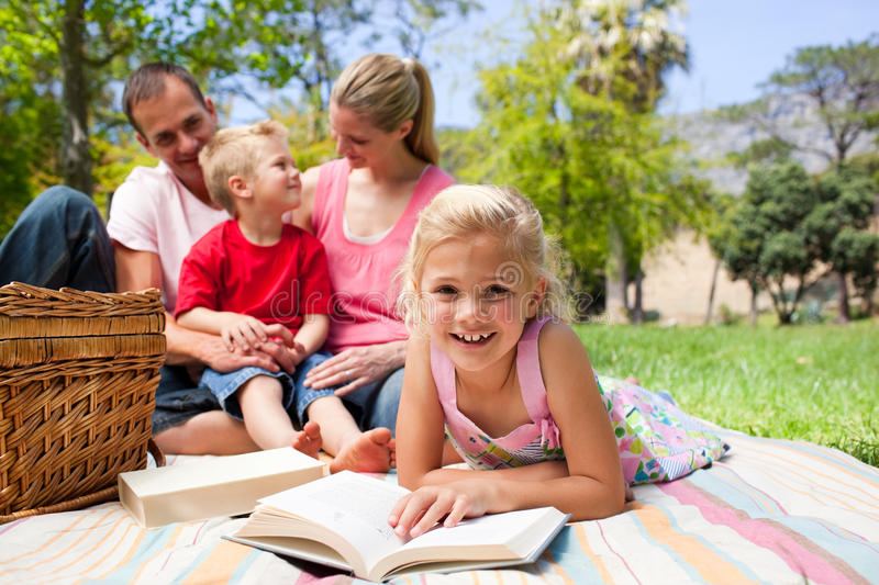 Blond Girl Reading Lying On A Picnic Tablecloth Royalty Free Stock Images