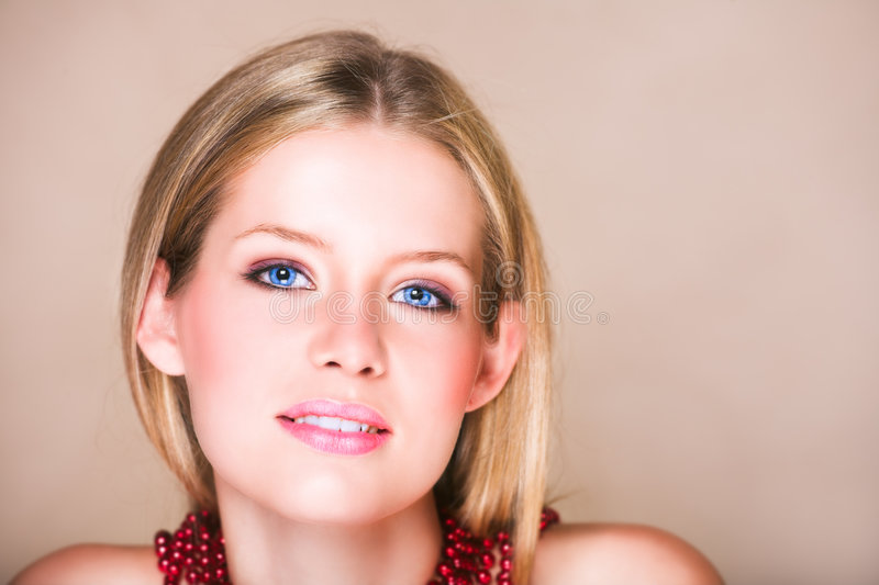 Blond girl in red necklace stock photography