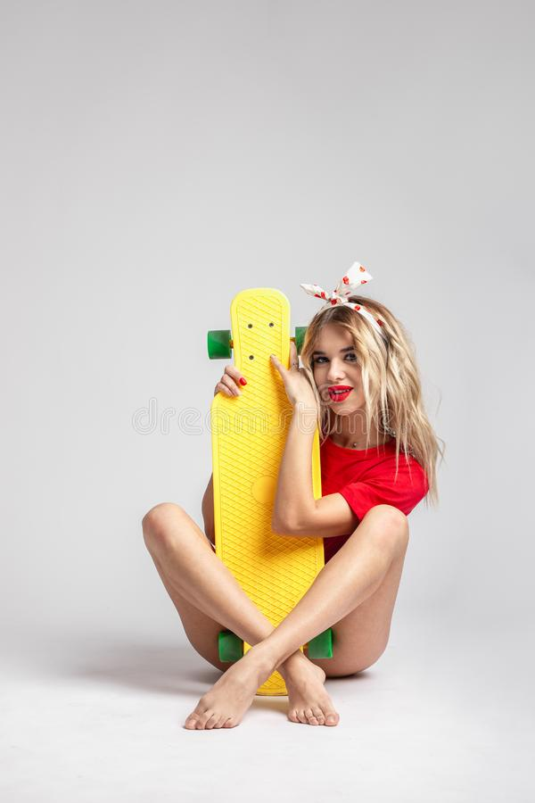 Blond girl in short denim shorts and a red t-shirt poses with a yellow skateboard sitting on the floor in the studio royalty free stock photo