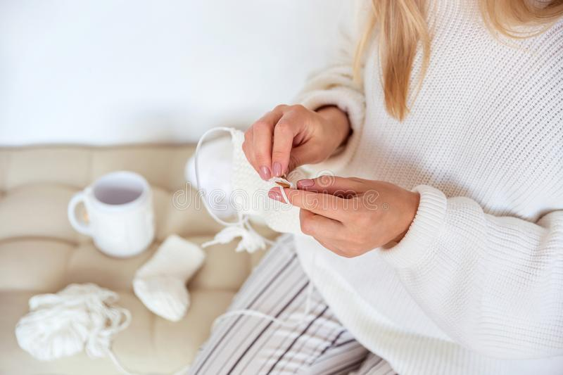 Blond girl sits on a soft pillow in a white sweater and knits baby socks from wool. Blonde girl sits on a soft pillow in a white sweater and knits baby socks royalty free stock images