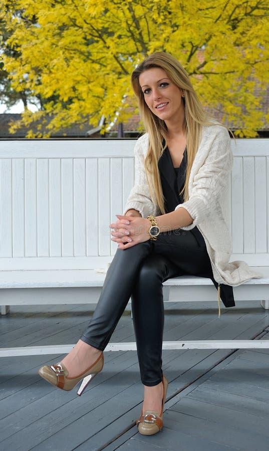 Blond girl sitting on bench