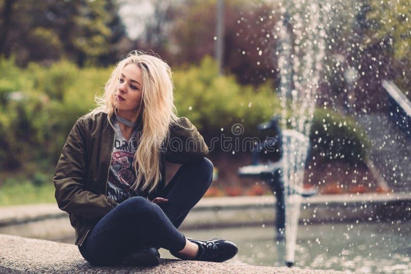Blond girl sitting beside fountain stock image