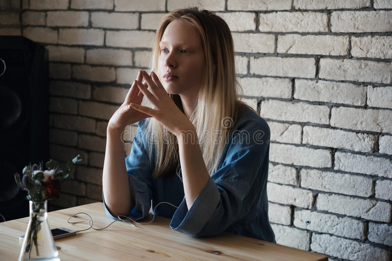 Blond girl is sitting with headphones and looking thoughtfully into the distance, combining in front of her fingers stock photography