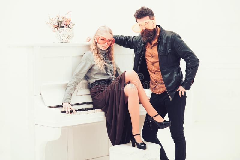 Blond girl sitting on white piano while bearded man in leather jacket standing next to her. Couple in enormous orange royalty free stock image