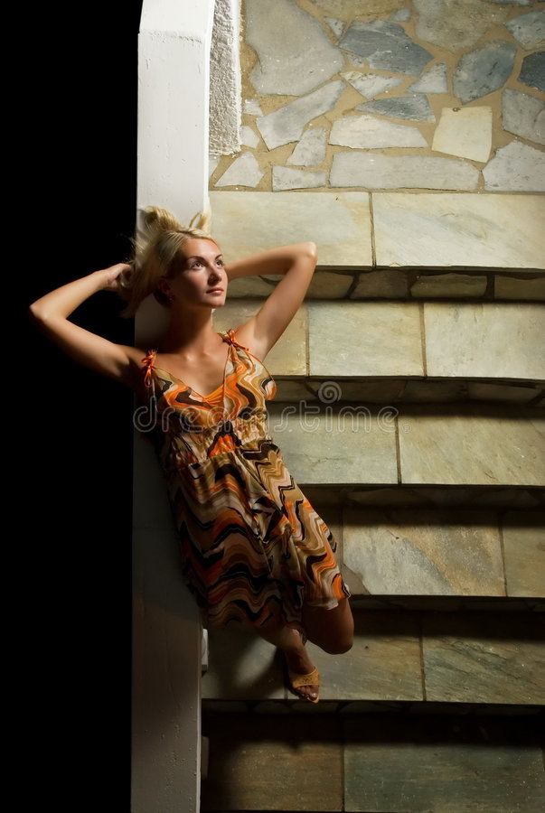 Blond girl on a stairs royalty free stock image