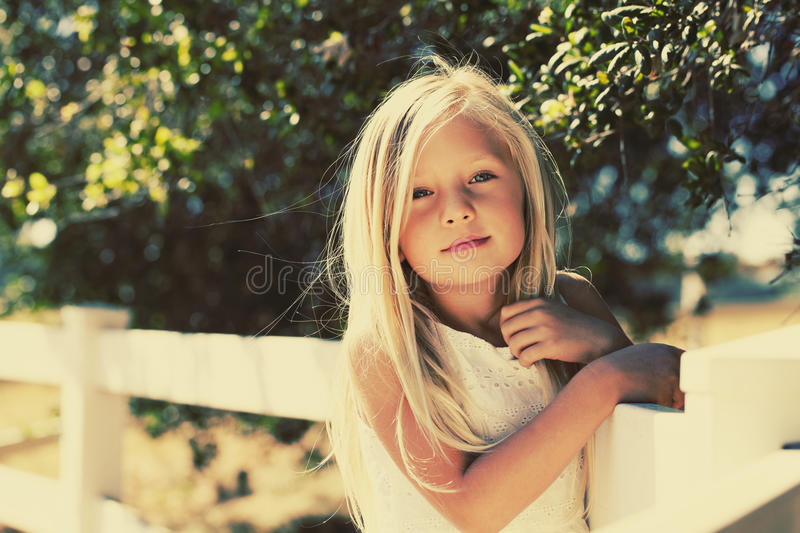 Blond Girl Summer Sun. A young girl with long blond hair blowing in breeze of early summer day stock image