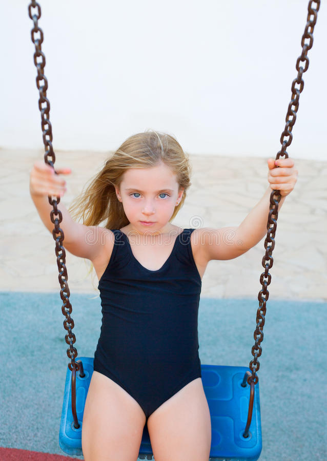 Blond girl swinging on blue swing with swimsuit royalty free stock images