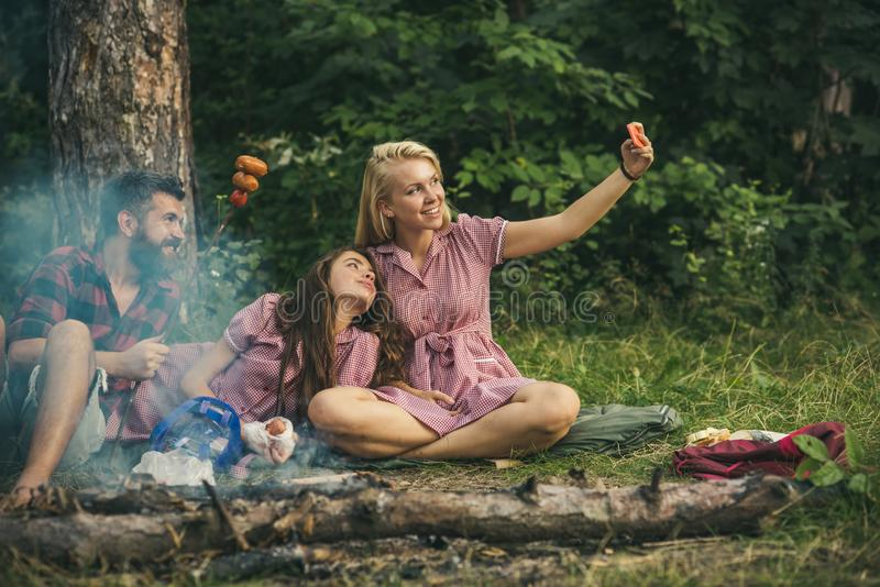 Blond girl taking selfie in forest. Smiling friends posing with sausages. Youngsters camping in woods royalty free stock images