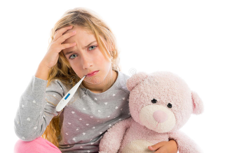 Blond girl with thermometer and flu cold in pyjama. Grumpy face with teddy bear royalty free stock images