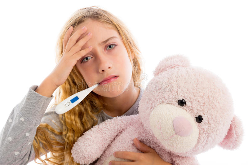 Blond girl with thermometer and flu cold in pyjama. Grumpy face with teddy bear stock image