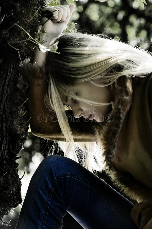 Blond girl thinking. Shot of a young blond woman with the head near a tree in act to look sad royalty free stock image