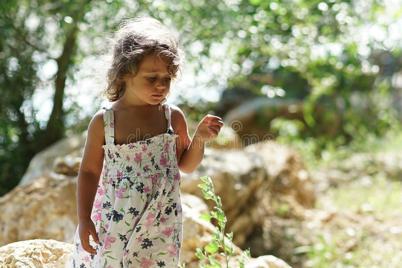 A blond girl of three years thoughtful near the Acheron River with its pristine nature in Epirus royalty free stock photography