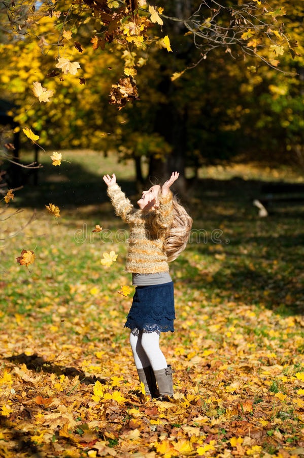 A blond girl throwing up the leaves royalty free stock photography