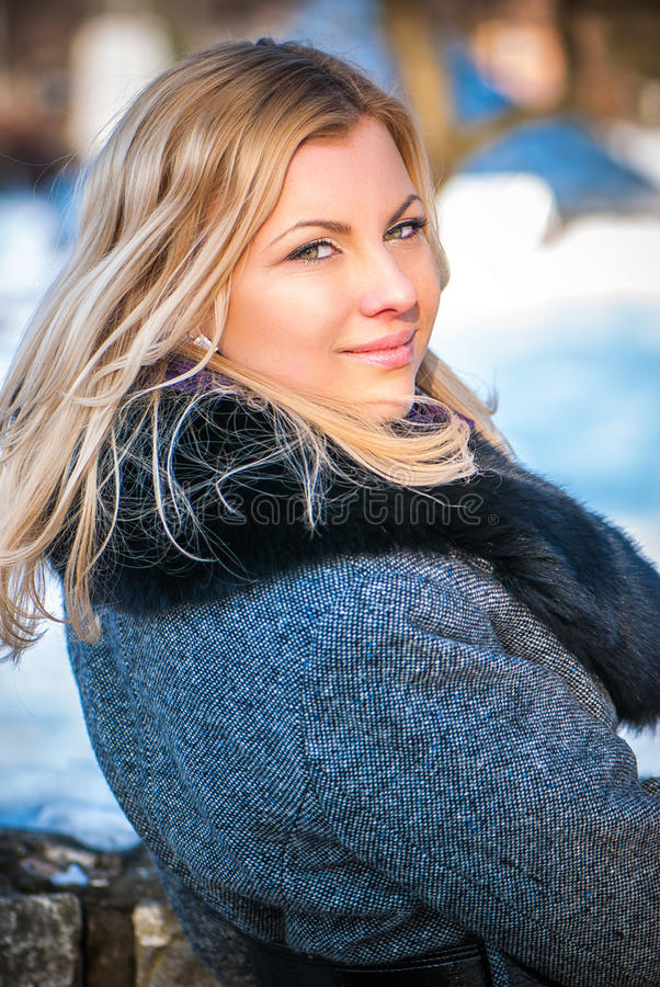 Blond girl wearing winter coat on the street royalty free stock images
