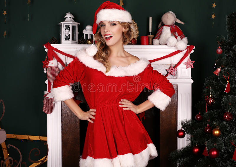 Blond girl wears Santa costume,posing beside Christmas tree and chimney royalty free stock image