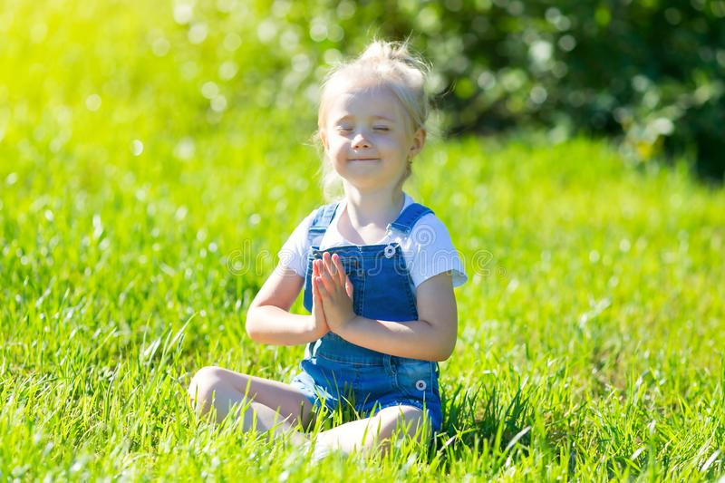 Little girl practices yoga on green grass. royalty free stock image