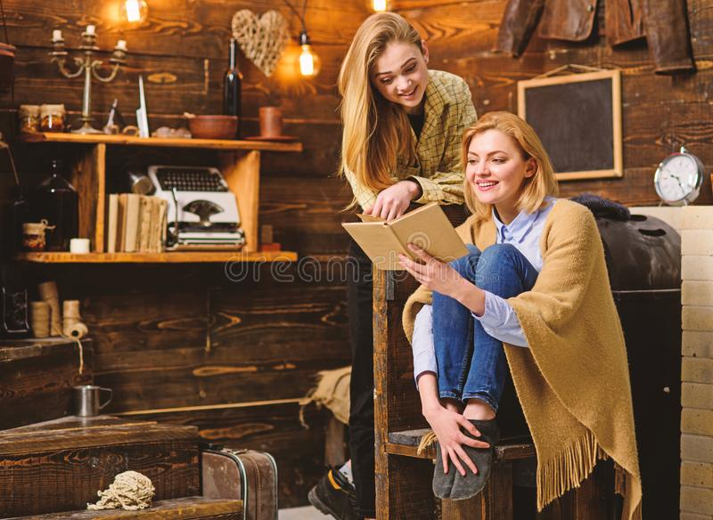Blond girls with bright smiles reading together. Woman wrapped in woolen blanket holding book. Mother and daughter royalty free stock image