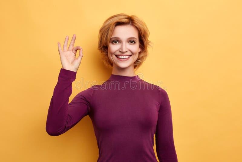 Blond gladlynt kvinna i den violetta rullhalsen som visar godkännandetecknet över gul bakgrund royaltyfri fotografi