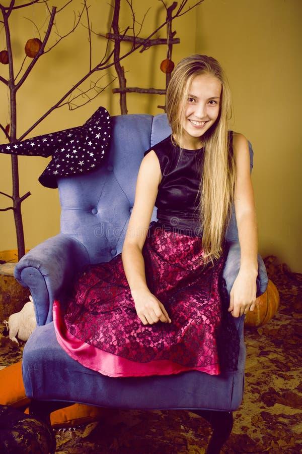 Blond gullig flicka i den halloween inre med pumpa som ler, tonårig allhelgonaaftonberöm, livsstilfolkbegrepp arkivfoto