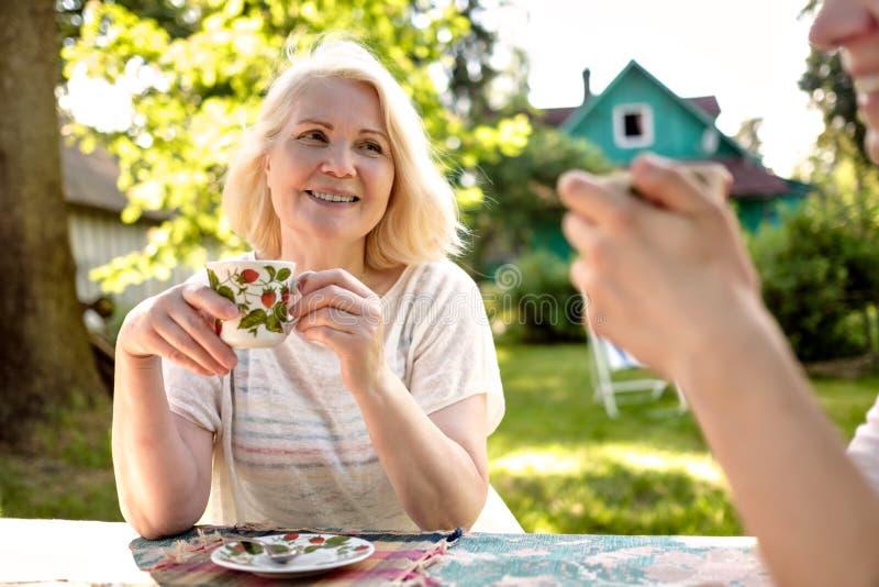 Blond härlig farmor som kopplar av med hennes familj på trädgården arkivbilder