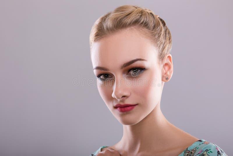 Blond härlig kvinnamodell över grå bakgrund härlig omsorg för stående arkivbild