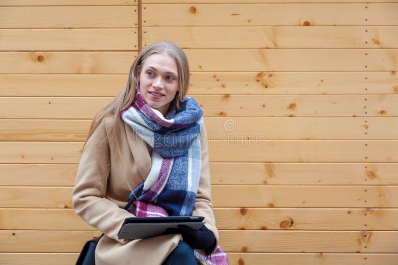 Blond härlig utomhus- kvinnainnehavminnestavla royaltyfri fotografi