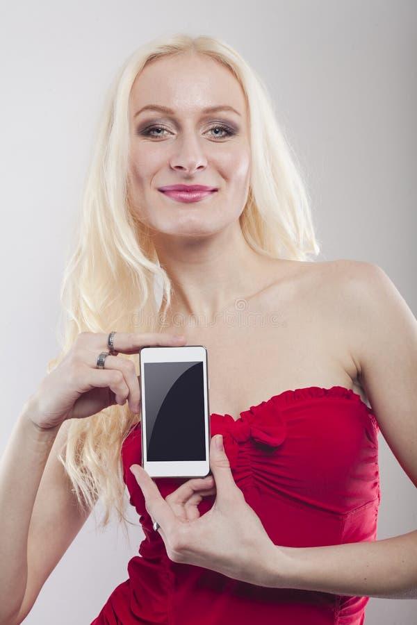 Blond hållande vit mobiltelefon i henne händer royaltyfria bilder