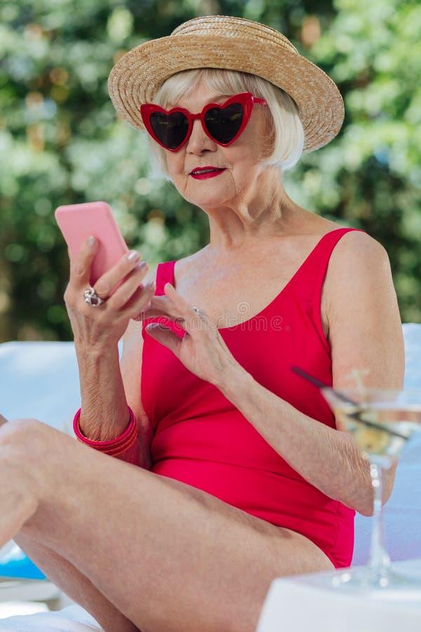 Blond-haarige reife Frau, die den roten ein Sonnenbad nehmenden Schwimmenanzug trägt lizenzfreies stockfoto