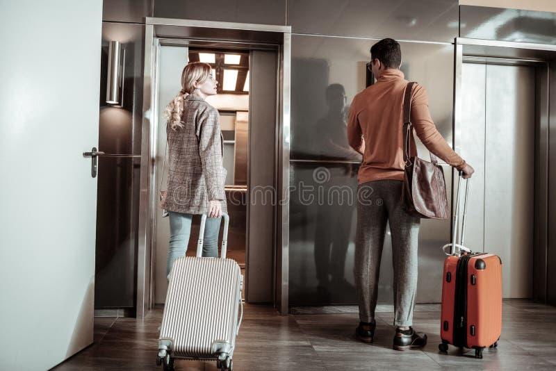 Blond-haariges Frausprechentschüss zu ihrem Ehemann, der für Geschäftsreise verlässt stockfotos
