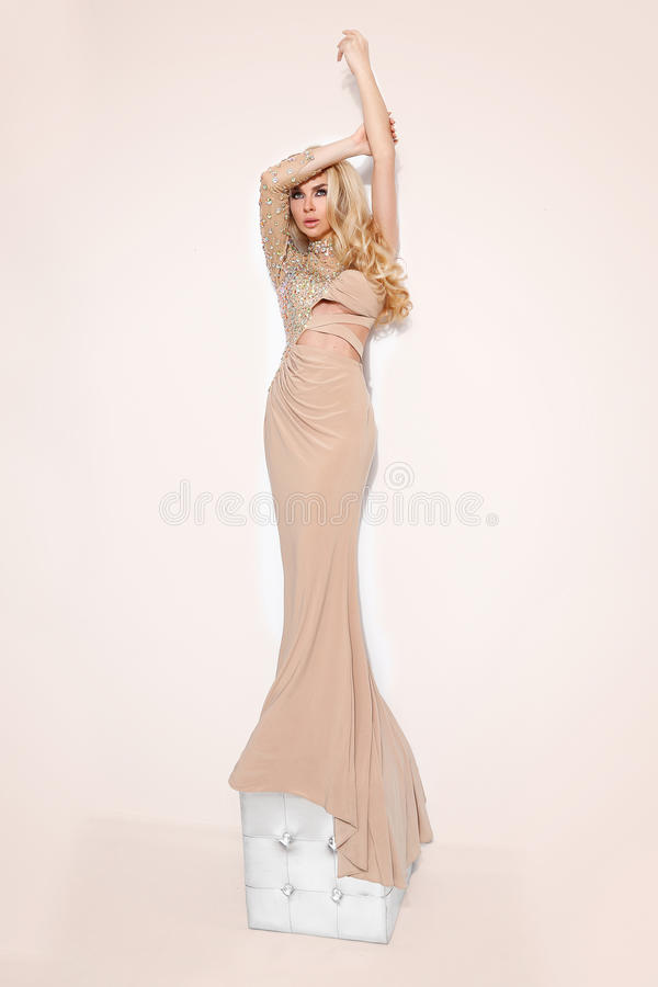 Blond hair beautiful young woman in long ballroom dress stock photo