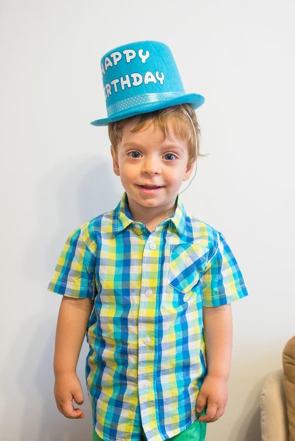 Happy birthday. Smiling  boy. Child portrait. Blond hair and blue eyes child portrait. Wearing a happy birthday hat royalty free stock photos