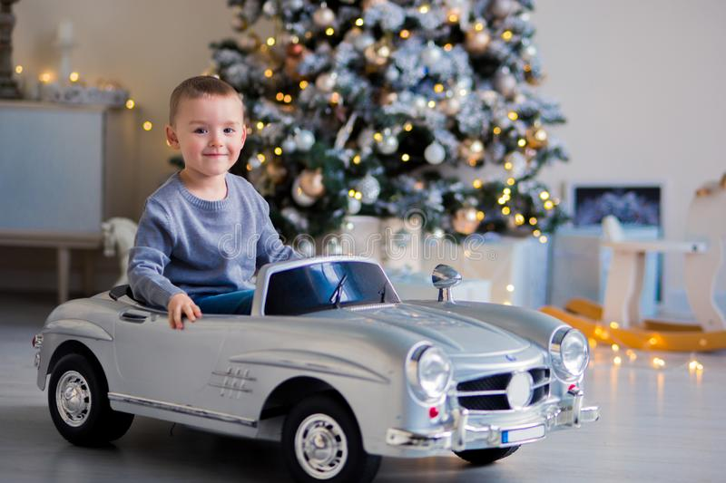 Blond-haired boy preschooler in a blue sweater smiles in a toy silver car. in the background - christmas tree, garland, lights.  stock image
