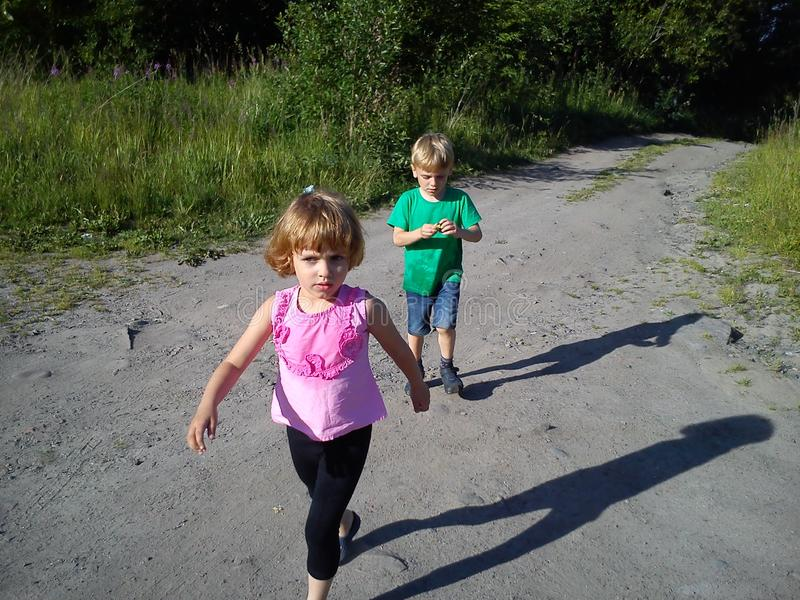 Blond-haired children walk on a dirt road in the summer. Boy in a green T-shirt. Girl in a pink blouse with frill. Brother and royalty free stock photography