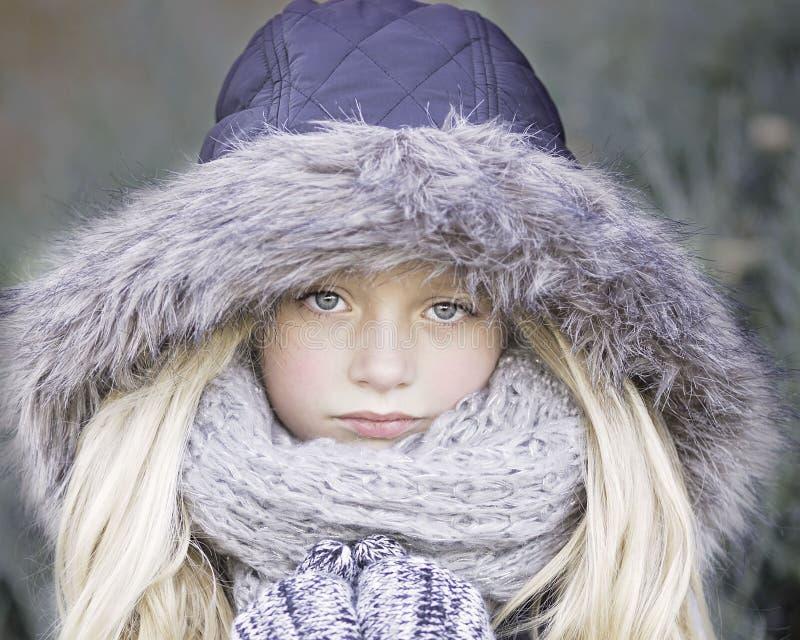 Blond haired flicka i lilavinteromslag royaltyfria foton