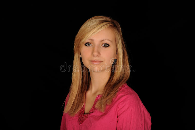 Blond haired teenager. Portrait of blond haired female teenager with black studio background stock images