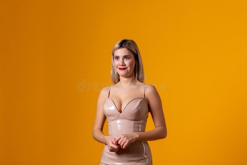 Blond haired ung kvinna med stora förvånade ögon som poserar på orange bakgrund arkivfoto