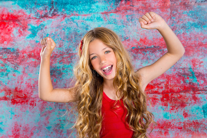 Blond happy children girl in red happy arms up. Blond happy children girl in red happy with arms up in grunge background stock photo