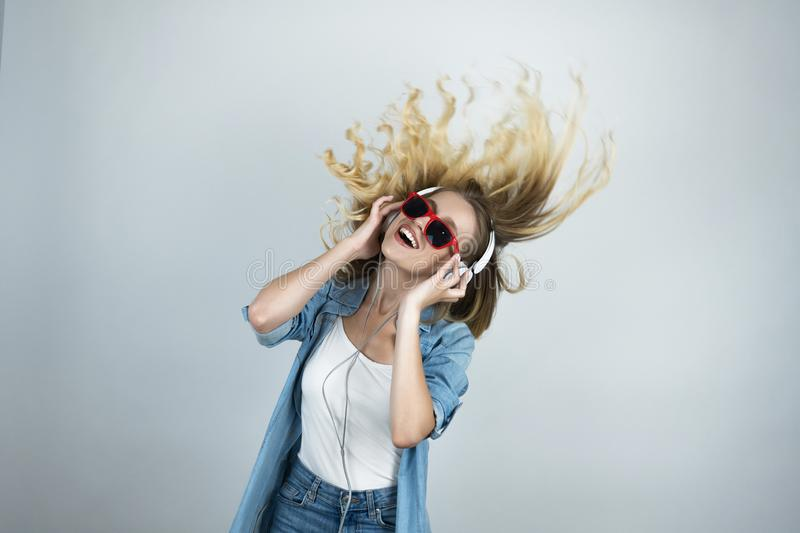 Blond happy woman in headphones and sunglasses listening to music dancing white isolated background in motion royalty free stock photography