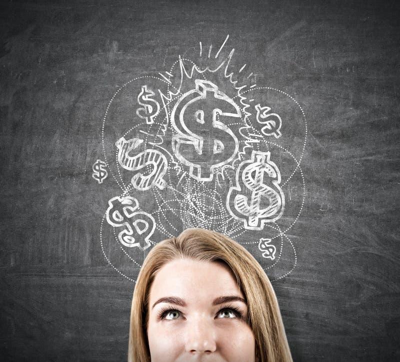 Blond head near chalkboard, shining dollar sketch. Close up of a blond woman`s head near a blackboard with a shining dollar sign sketch depicted on it. Concept stock photos
