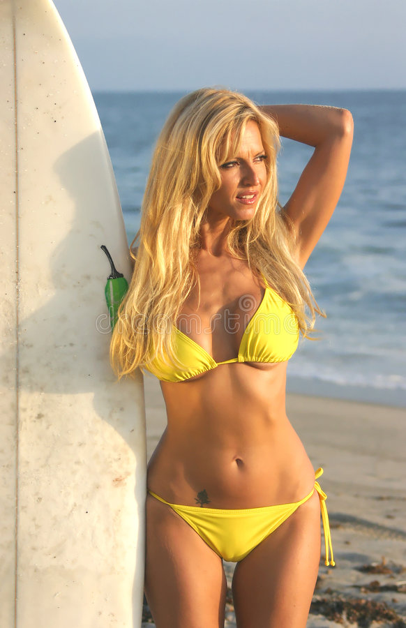 Blond holding a Surfboard on the beach royalty free stock image