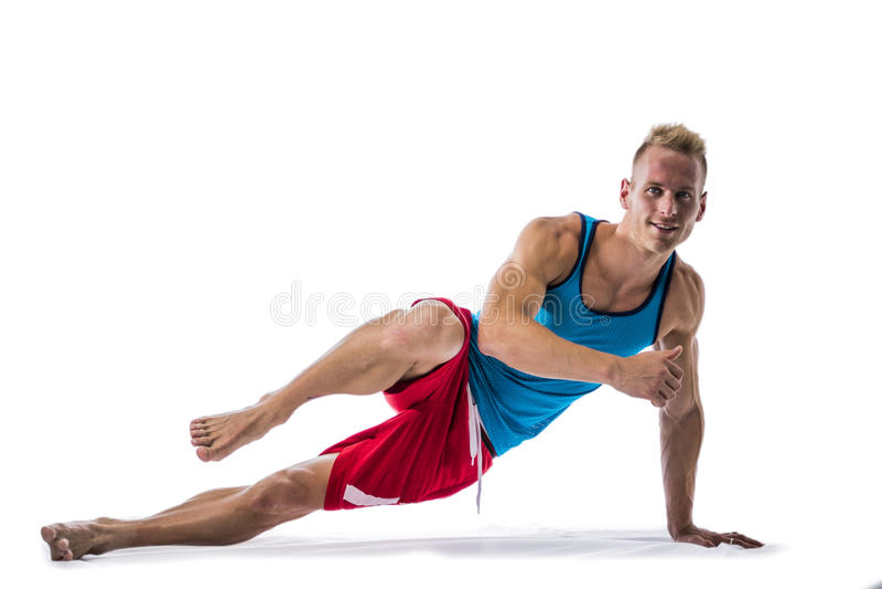 Blond idrotts- ung man som exercizing på golvet royaltyfri bild