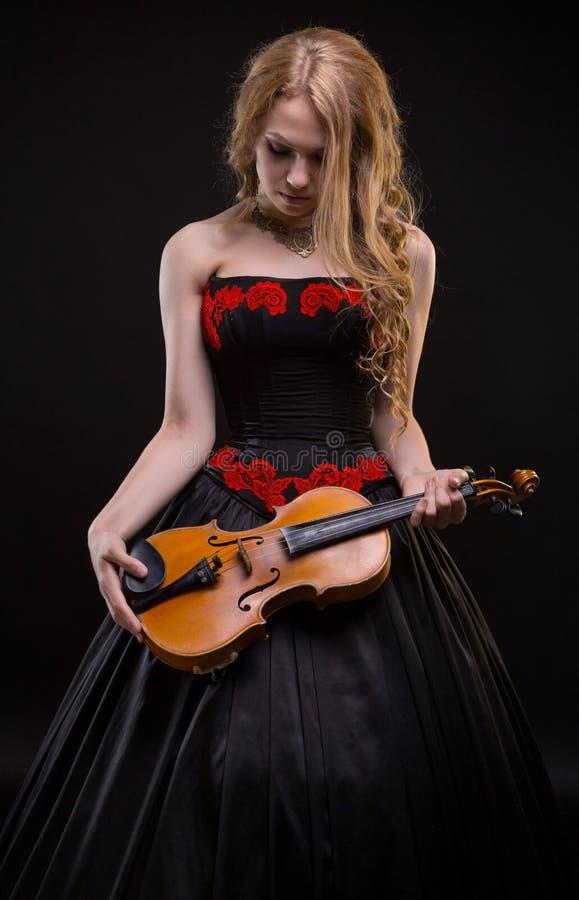 Blond jong meisje in overlegkleding met de viool stock afbeelding