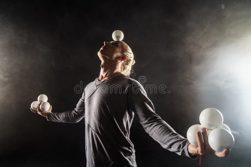 Blond juggler keep in balance white balls on black background royalty free stock photography