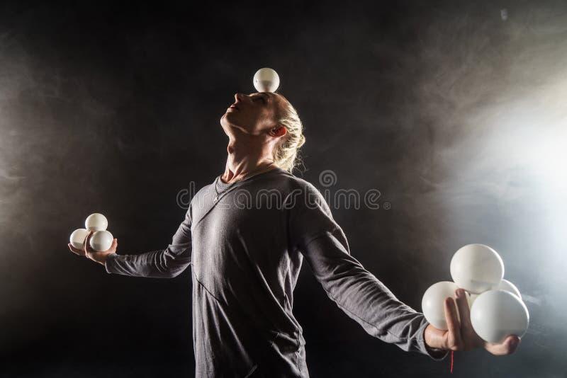 Blond juggler utrzymanie w balansowych białych piłkach na czarnym tle fotografia royalty free