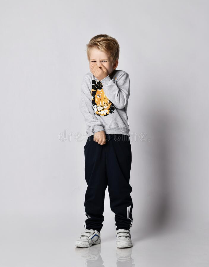 Free Blond Kid Boy In Black Pants And Shirt With Lion Print Giggles Covering His Mouth And Nose With Hand Royalty Free Stock Photography - 195353517